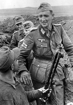 Army Reserve Captain Helmuth Ott speaks with young soldier in the trenches near Yass, Romania. Ott wears the Knight's Cross. He was killed in action on April 24, 1945, six days before Hitler committed suicide. Note the Mg42 machine gun in the foreground.