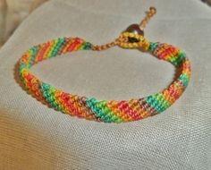 Geknüpftes Armband in Makrameetechnik in schönen Farben: braun, hellbraun, rot, orange, apfelgrün, grün.  Als Verschluss dient eine Holzperle  ...