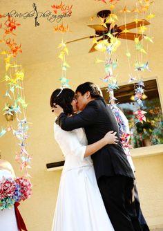 Hand folded rainbow paper cranes as an altar backdrop at this backyard Las Vegas wedding | Handmade Rainbow Wedding Full of Love | Photos: Ali McGhie
