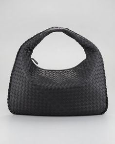 "Black woven intrecciato napa leather. Gunmetal hardware. Zip closure. Handles have 5"" drop. Suede interior. Interior zip pocket. Includes hand mirror. 9 1/2""H 16""W x 1""D. Made in Italy."