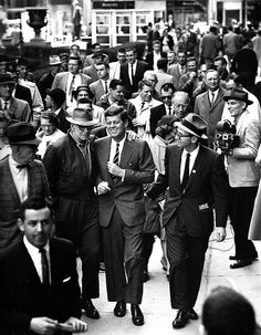"""Jacques Lowe caught this image, a favorite of Jack's, during an April 1960 stop in Charleston, West Virginia, just days before Kennedy won the primary. JFK has been claimed by a supporter and is enjoying it, as local pols and reporters follow along. Years later, Caroline Kennedy Schlossberg presented a copy of this photo to President Bill Clinton, who put it in his """"Kennedy corner,"""" a collection of Kennedy family memorabilia in Clinton's private study on the second floor of the White House."""