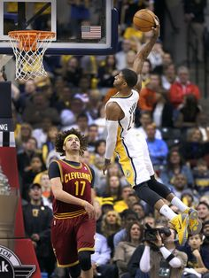 Indiana Pacers Paul George goes high to dunk on Cleveland Cavaliers Anderson Varejao. This would make a great poster on my wall!