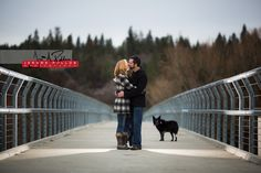 Hilary and Deven's fur child Daisy keeps a watchful eye as they get cozy on top of the bridge. #engagement #portrait #couple #spokane #washington #kiss #outdoors #nature #dog #pet #ontopofthebridge