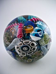 Abstract placement of murrini create an art glass world a kin to the living organizms of an ocean reef. Ocean Reef Paperweight by Michael Egan