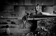 Todas las mañanas, niños de una barriada cercana llegan en pequeños grupos, descalzos y con esterillas y escobas empiezan a limpiar el espacio bajo un puente ferroviario de metro, que será su escuela para el resto de la tarde. Foto: Altaf Qadri.