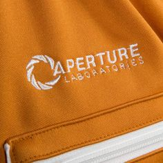 This is the Portal 2 Aperture Test Subject Premium Track Jacket. It's knitted from 100% Polyester and has a custom metal logo zipper pull, chest logo embroidery and back graphic print. A sweet track j