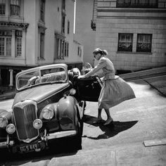 A woman parking her 1950 Riley RMD drophead coupé on Mason St. in San Francisco, just down the hill from the Mark Hopkins hotel / photo by Fred Lyon, 1953.