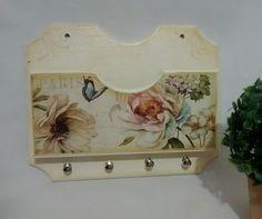 Produzido em mdf, com pintura na cor marfim, e detalhes na cor ocre. Com decoupagem no tema floral e pinos de metal para chaves.  Medidas 24cm de largura x 19cm de altura.