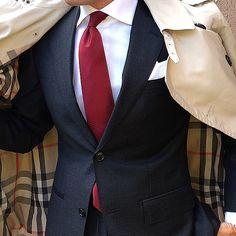 A classic #Burberry trench #coat is a sleek and sophisticated statement piece for the modern man. I like how the red tie picks up the subtle red detail in the plaid.