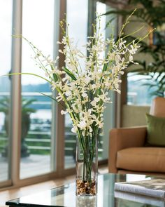 """The graceful oncidium orchid stems and wispy grass add a carefree  personality to this casual design. Its supple natural orchid beauty and  detail is accentuated in a 9.5"""" tall square glass vase with stone and  clear acrylic water."""