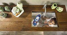 Un volume découpé dans un plan de toilette en bois brut de 8 cm d'épaisseur, un fond incliné en verre transparent et voilà une vasque originale qui crée la surprise.