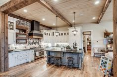 The stunning eat-in kitchen has modern amenities such as marble counter tops and wooden bar stools while still maintaining a rustic appearance