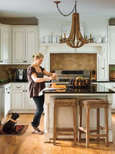 love the color scheme of this kitchen...white cabinets, black granite countertops, sandy brown backsplash, wicker bar stools