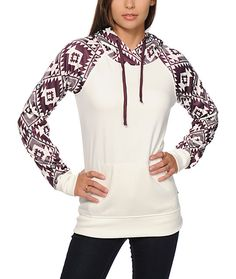 From the mountains to the streets, keep warm with the style of this long slim fit tech fleece hoodie that features a solid cream colored body accented with a burgundy tribal print hood and sleeves.