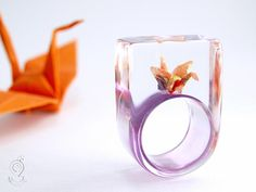 Shimmy luck – extraordinary origami crane ring with self-made folded mini-crane made of colorful paper on a purple ring made of resin
