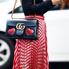 """Gucci shiny leather shoulder bag with embedded red hearts. Antiqued golden hardware. Sliding chain strap can be doubled, 12""""-14.5"""" drop. Flap top with interlocking GG snap closure. Lips detail at back. Interior, center zip compartment; zip pocket. Cotton linen lining. 6""""H x 11""""W x 3""""D. """"GG Marmont"""" is made in Italy. Suno midi skirt in metallic knit. Column silhouette. Hem hits above ankle. Banded waist. Acrylic/metallic/nylon. Made in Romania.  Women nmbandbags BLACK MULTI nmstreetstyle…"""