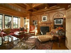 The waxed Italian walnut walls, richly carved bookcases, fireplace mantel, and coffered ceiling provide a warm and cozy environment with lake and garden views to the south and west.