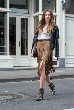 20 Inspiring Outfits That Show You How to Rock Fringe This Spring - tan suede skirt with fringe detail, worn with a graphic t-shirt, over-the-shoulder leather jacket, + pointy toe ankle boots