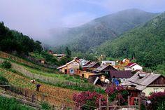Listvyanka village, Lake Baikal  Houses in valley & villagers working in Garden in Listvyanka village on Lake Baikal