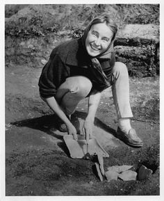"""Norwegian archeologist Anne Stine Moe Ingstad (1918-1997) discovered the remains of a Norse settlement in Newfoundland and was author of The Norse Discovery of America (1977). In this photograph distributed by the National Geographic Society, Ingstad """"examines a fire pit at the site of what is believed to be a Norse house dating from about A.D. 1000""""."""