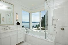 Sleek white bath features polished nickel mirror over extra-wide single vanity accented with crystal knobs topped with white marble next to tiled bathtub with marble surround showcasing amazing view paired with attached shower with seamless glass door.