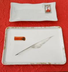 Two ceramic pen trays. The one in front has a trompe l' oeil  motif of a quill pen and a piece of red sealing wax that has been burned on one end. The other pen tray looks like an envelope with a stamp._Judith Walker's Collection