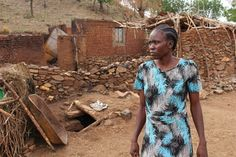 Hamida Osman in front of her incinerated home and the fox-hole in which her 2-year-old, Safarina, was killed. (Image: Nick Kristof)