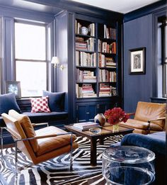 Navy blue walls with quirky zebra print rug and light brown chairs to soften the impact
