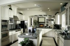 Stunning white U-shaped kitchen with custom cabinets and stainless steel appliances.