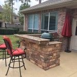 Big Green Egg grill built into island with bar and snazzy red counter stools in outdoor kitchen by Outdoor Homescapes of Houston.