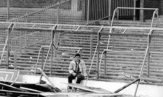 A Liverpool fan sits by the damaged fencing in the aftermath of the Hillsborough disaster.