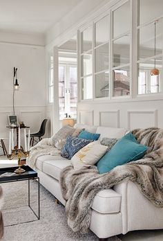 A pretty cozy living room in Scandinavian style. Love the white floors, white walls and white furniture with a dash of black and gold accents