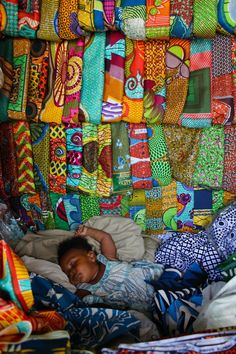 Africa | A little child sleeping among African wax print fabrics.  Cape Coast, Ghana. | ©photographer unknown