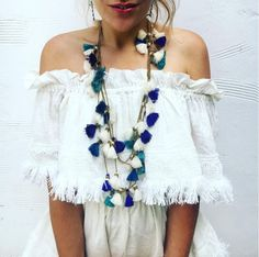 The Dara Tassel Necklace takes any basic outfit to anything but. Handmade double strand goldtone beaded necklace punctuated by a myriad of colorful ocean blue thread tassels. Adjustable Also available