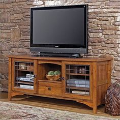 """Bowery Hill 63"""" TV Stand in Abbey Oak. Features: Holds up to 55"""" Televisions weighing 135 lbs Or less; Two adjustable shelves behind each framed door with faux leaded, safety-tempered glass for holding audio/video equipment ; Drawer with metal runners and safety stops holds DVDs and CDs ; Quick and easy assembly with patented T-lock drawer system ; Abbey Oak finish on this entertainment credenza . Specifications: Product Dimensions: 27.75""""H x 63.375""""W x 19.25""""D; Weight: 162 lbs."""