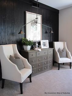 accent wall looks like reeds painted glossy black, grey dresser, dual brass light fixture
