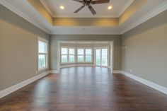 Large master bedroom with a big bay window and tray ceilings.
