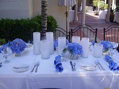 love the blue flowers with white pillar candles or white candle holders