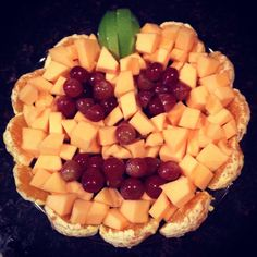 Halloween fruit tray. Pumpkin shaped with cantaloupe with border of oranges and face of red grapes and green apple stem.