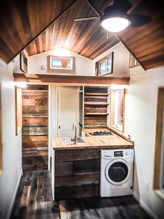 This is the Kootenay tiny house on wheels by Green Leaf Tiny Homes. From the outside, you'll notice half of the house features stained wooden siding and the other half has corrugated black me…