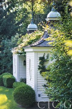 A Bloom With A View - Twin pool houses are nestled in boxwood with pyracantha climbing the walls and topped with copper finials through Bob Withington Antiques.