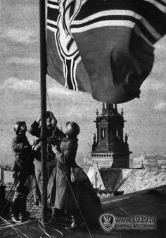 Krakow, Poland - September 1939 - German soldiers raise flag with swastika.