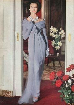 October Vogue 1956    One of the chiffon triumphs of Dior's collection - a dress from his new palette of milky colours. The drapery collects in a high loose knot under the bosom and from there it just drifts away.    Part of the look; sheathed chiffon gloves, chiffon covered shoes and milk-blue and pearl mixed beads