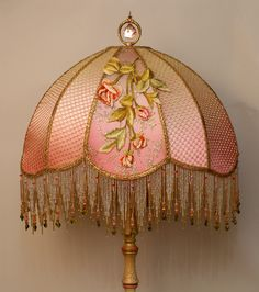 A stately traditional Victorian wood lamp base has been hand-painted and holds a hand-dyed Carousel silk lampshade. The shade is ombre-dyed from pale gold into peachy pink. The shade is covered on the sides with gold metallic mesh and the front panels with antique metallic gold lace and then overlaid with beautiful silk appliques acquired in France.    The shade has glass and hand beaded fringe in matching tones and is topped with a beautiful jeweled finial.