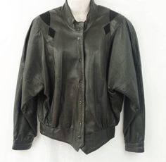1980s Etienne Aigner black leather jacket for women.It features a snap closure front,suede inserts and a stand up collar.The exterior is 100% leather