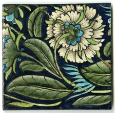 6 inch tile with chrysanthemum, green swirling leaves, splashes of turquoise colour.  On a dark blue ground.  De Morgan Sands End Fulham Pottery impressed mark on reverse
