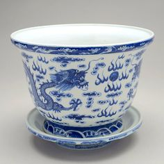 Three Blue and White Planters with Bases, Each painted with confronting five-clawed dragons centered by a flaming pearl and amidst flames and clouds, all above waves and beneath a band of ruyi-heads, the drilled base bearing Yongzheng and Qianlong marks, matching under trays. 19th/20th Century Tallest: 6 5/8 inches