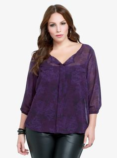 Billowy sleeves with elastic cuffs, front pockets and a sewn-up front with an open collar detail this sheer pullover top. We've patterned the purple chiffon with a tonal rose print.