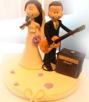Topo de bolo noivinho guitarrista e noivinha cantora em biscuit