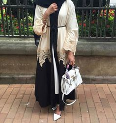 A stunning abaya of black and white nida with a gold lace finish giving it class and sophistication. Perfect for occasional wear! The abaya also ha...